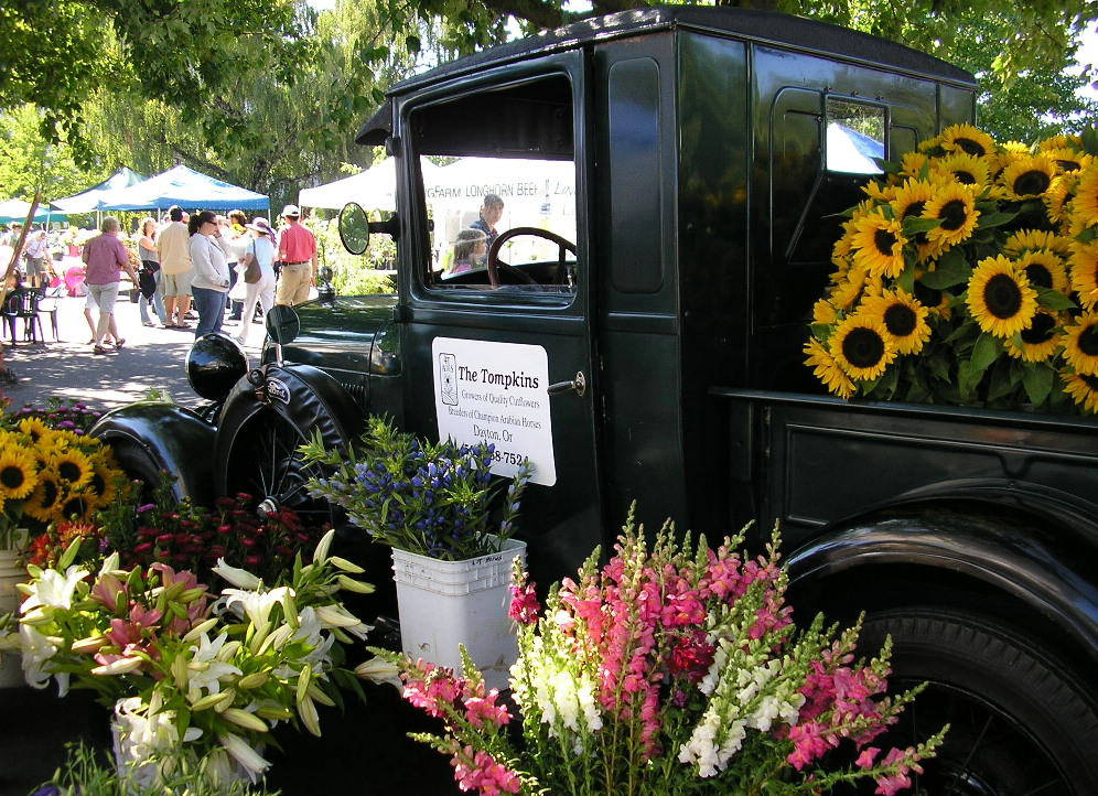 Some flowers and visitors at the Salem Saturday Market.