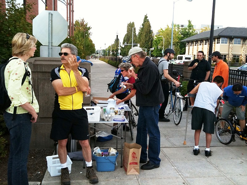 Local bike commuters chat, help each other with bikes, eat pastries, pizza, fruit and drink coffee at today's Breakfast on Bikes in downtown Salem.