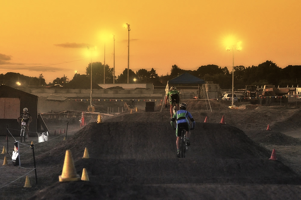 Racers heading through the BMX track as the sun fades and the lights come up on the track