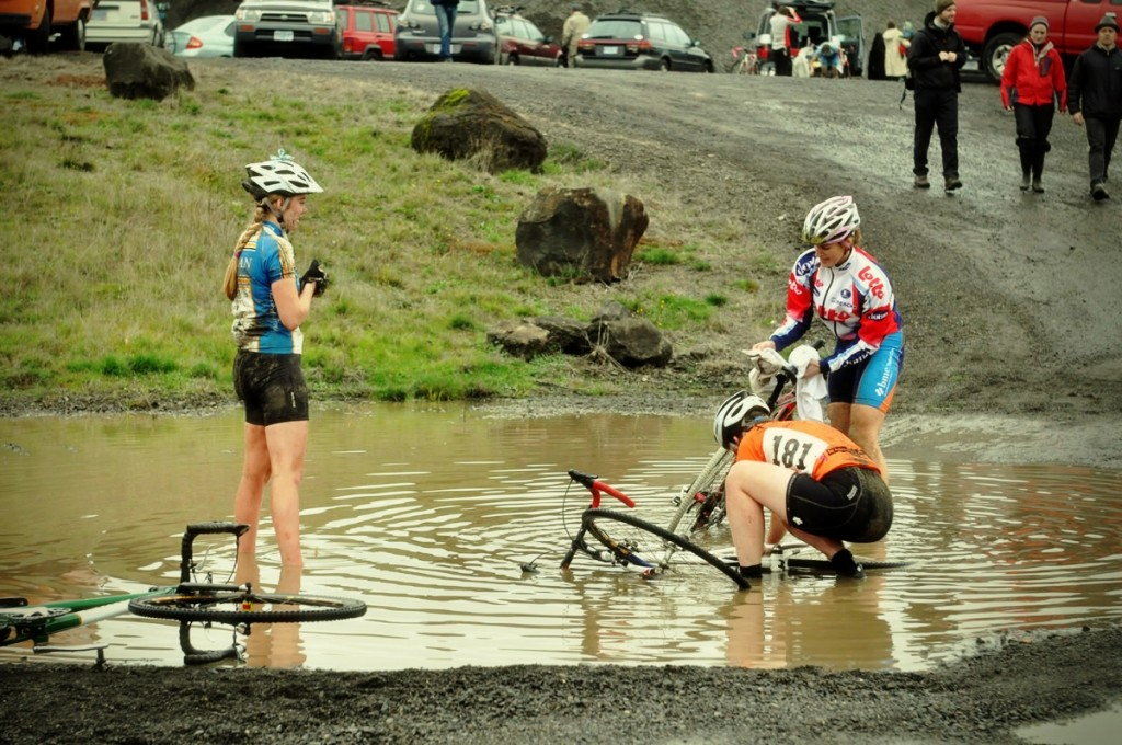 "Racers ""cleaning"" their bikes in the ginormous mud puddles at Barton Park."